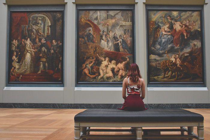 Femeie cu spatele pe fundal de tablouri